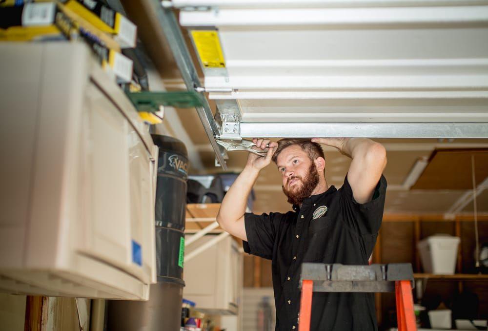 Precision technician working on garage door